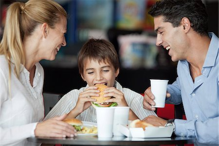 family table eating together - Boy eating hamburger in fast food restaurant with his parents Stock Photo - Premium Royalty-Free, Code: 632-06118493