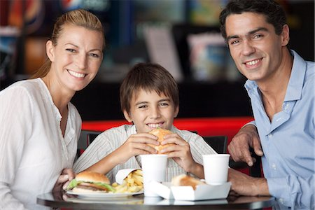 family table eating together - Family eating together in fast food restaurant, portrait Stock Photo - Premium Royalty-Free, Code: 632-06118521