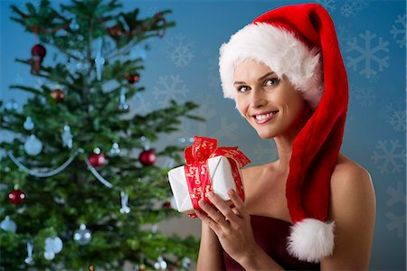 snowflakes  holiday - Woman wearing Santa hat and holding Christmas present, portrait Stock Photo - Premium Royalty-Free, Code: 632-06118583