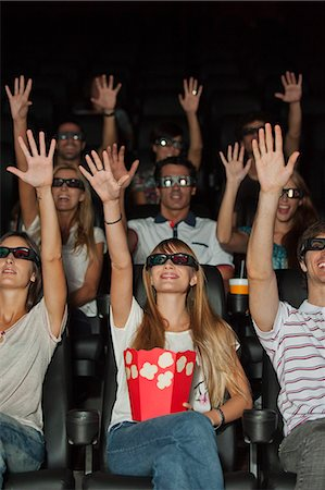 front row seat - Audience wearing 3-D glasses in movie theater, arms reaching up Stock Photo - Premium Royalty-Free, Code: 632-06118630