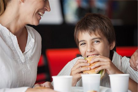 family table eating together - Boy eating hamburger in fast food restaurant Stock Photo - Premium Royalty-Free, Code: 632-06118651