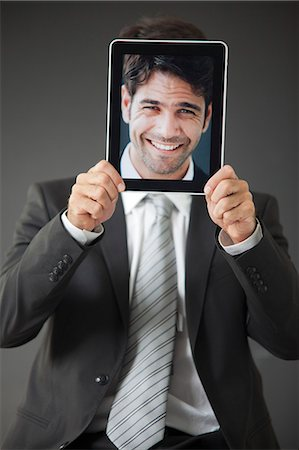 dece11 - Man holding smiling photograph in front of his face Stock Photo - Premium Royalty-Free, Code: 632-06118666