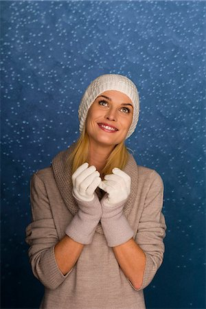 Woman wearing knit hat and gloves in front of snowy background, portrait Stock Photo - Premium Royalty-Free, Code: 632-06118762