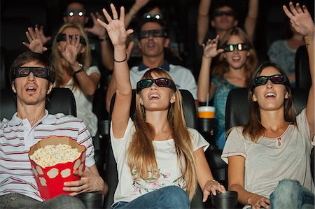 front row seat - Audience wearing 3-D glasses in movie theater, arms reaching out Stock Photo - Premium Royalty-Free, Code: 632-06118853