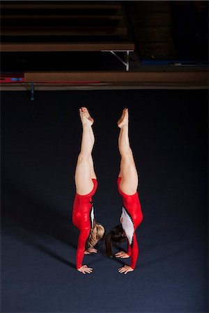 Female gymnasts performing handstands back to back Stock Photo - Premium Royalty-Free, Code: 632-06118885