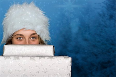 Young woman peeking over stack of Christmas gifts, portrait Stock Photo - Premium Royalty-Free, Code: 632-06118891