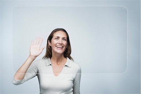 Woman waving at large transparent screen Stock Photo - Premium Royalty-Free, Code: 632-06317155