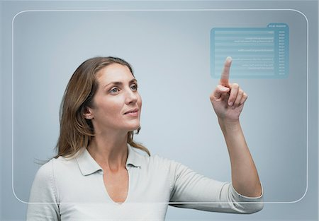 Woman looking at her schedule of the day on advanced touch screen interface Stock Photo - Premium Royalty-Free, Code: 632-06317170