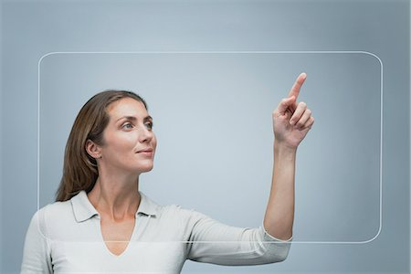 Woman using large transparent touch screen Stock Photo - Premium Royalty-Free, Code: 632-06317221