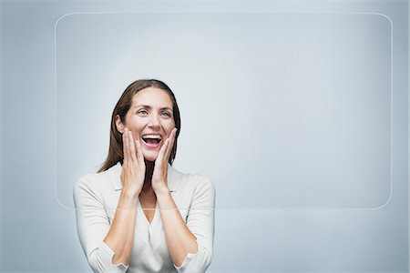 surprised - Woman looking at large transparent touch screen with surprised expression on face Stock Photo - Premium Royalty-Free, Code: 632-06317239