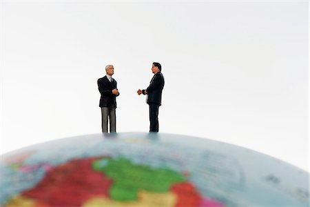 Businessman figurines standing on top of globe Stock Photo - Premium Royalty-Free, Code: 632-06317332