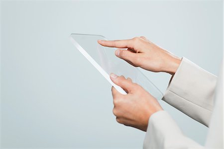 Woman using transparent digital tablet, cropped Stock Photo - Premium Royalty-Free, Code: 632-06317383