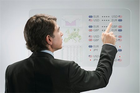 Businessman using advanced touch screen technology to view business data Stock Photo - Premium Royalty-Free, Code: 632-06317397