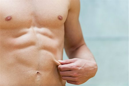 Barechested man pinching waist, mid section Stock Photo - Premium Royalty-Free, Code: 632-06317527