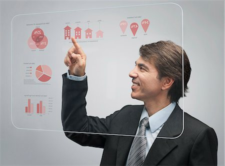 Businessman using advanced touch screen technology to view sales data Stock Photo - Premium Royalty-Free, Code: 632-06317520