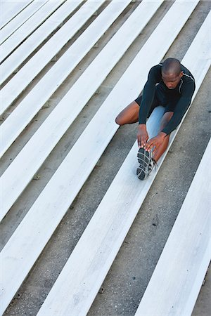 Man stretching on bleacher, high angle view Stock Photo - Premium Royalty-Free, Code: 632-06317537