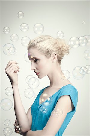 Young woman surrounded by bubbles, portrait Stock Photo - Premium Royalty-Free, Code: 632-06317574