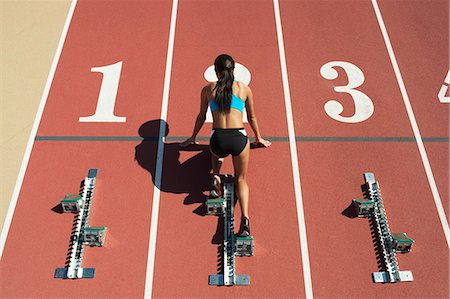 Female athlete in starting position on running track, rear view Stock Photo - Premium Royalty-Free, Code: 632-06317636