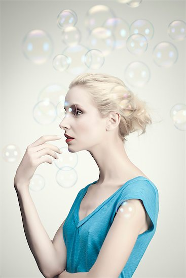 Young woman surrounded by bubbles, portrait Stock Photo - Premium Royalty-Free, Image code: 632-06317672