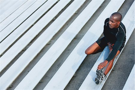 Man stretching on bleacher, high angle view Stock Photo - Premium Royalty-Free, Code: 632-06317699