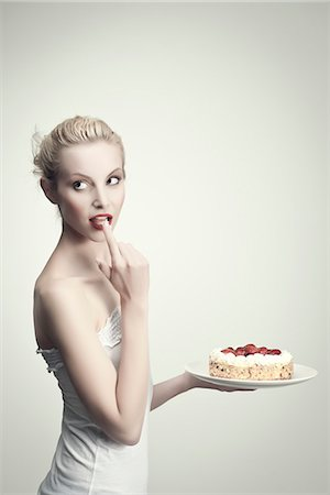 Young woman holding strawberry cake, licking cream off finger, portrait Stock Photo - Premium Royalty-Free, Code: 632-06317725