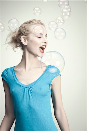 Young woman surrounded by bubbles with mouth open Stock Photo - Premium Royalty-Free, Code: 632-06317864
