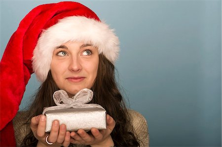 Young woman holding Christmas present, looking up in thought Stock Photo - Premium Royalty-Free, Code: 632-06354180