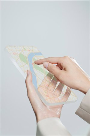 Woman using transparent digital tablet with touch screen to view map, cropped Stock Photo - Premium Royalty-Free, Code: 632-06354447
