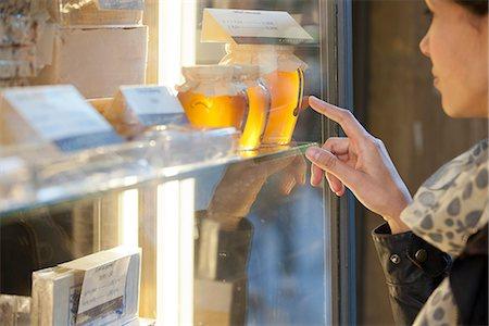 desire - Woman looking at jars of honey in shop window Stock Photo - Premium Royalty-Free, Code: 632-06404216