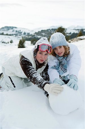Teenage girls rolling snowball together, portrait Stock Photo - Premium Royalty-Free, Code: 632-06404417