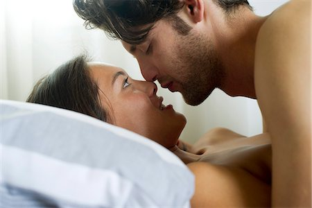 Young couple romancing in bed, side view Stock Photo - Premium Royalty-Free, Code: 632-06404474