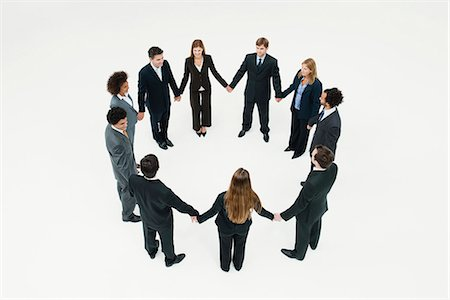 Businessmen and businesswomen standing together in circle holding hands Stock Photo - Premium Royalty-Free, Code: 632-06404613