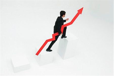 Businessman ascending steps holding arrow pointed upward Stock Photo - Premium Royalty-Free, Code: 632-06404626