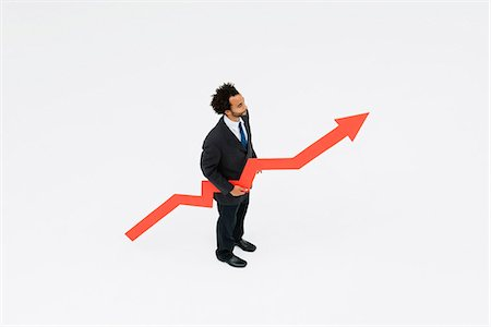 Businessman with arrow pointed upward projecting financial growth Stock Photo - Premium Royalty-Free, Code: 632-06404623