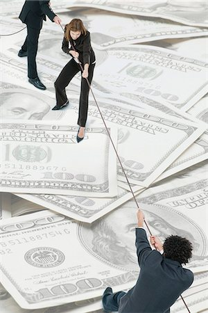 Executives playing tug-of-war on top of pile of one-hundred dollar bills Stock Photo - Premium Royalty-Free, Code: 632-06404681