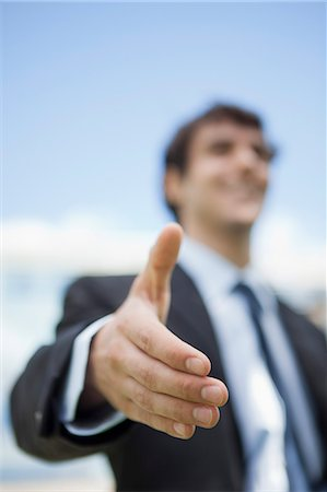 Businessman extending hand for handshake, low angle view Stock Photo - Premium Royalty-Free, Code: 632-06779111