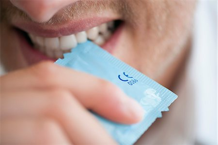 Man tearing open condom wrapper with his teeth Stock Photo - Premium Royalty-Free, Code: 632-06779139