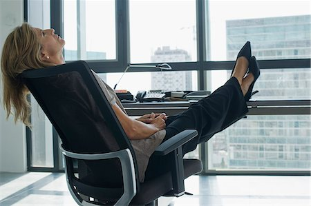 Businesswoman leaning back in chair with feet up on desk Stock Photo - Premium Royalty-Free, Code: 632-06779309