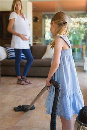 Little girl vacuuming, pregnant mother in background Stock Photo - Premium Royalty-Free, Code: 632-06967664
