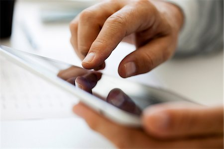 Man using touch screen on digital tablet, cropped Stock Photo - Premium Royalty-Free, Code: 632-06967663