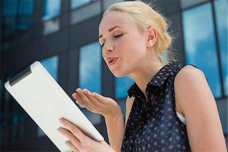 Young woman blowing kiss at digital tablet Stock Photo - Premium Royalty-Free, Code: 632-07161250