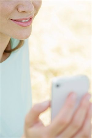 Woman using smartphone outdoors, cropped Stock Photo - Premium Royalty-Free, Code: 632-07161362