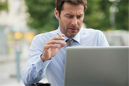 Businessman smoking while using laptop computer outdoors Stock Photo - Premium Royalty-Free, Code: 632-07161462