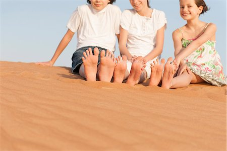 Children sitting on sand dune Stock Photo - Premium Royalty-Free, Code: 632-07161475