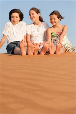 Children sitting on sand dune Stock Photo - Premium Royalty-Free, Code: 632-07161476