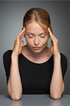 Young woman holding head, eyes closed Stock Photo - Premium Royalty-Free, Code: 632-07495000