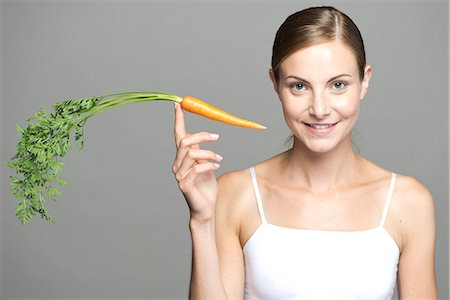 fingers holding - Young woman balancing carrot on fingertip Stock Photo - Premium Royalty-Free, Code: 632-07495062