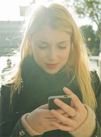 Young woman using smartphone Stock Photo - Premium Royalty-Free, Code: 632-07539878