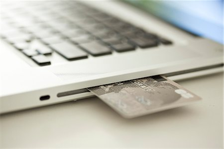 Credit card sticking out of side of laptop computer Stock Photo - Premium Royalty-Free, Code: 632-07539887