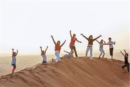 Group of people standing on top of desert dune with arms raised in air Stock Photo - Premium Royalty-Free, Code: 632-07539890